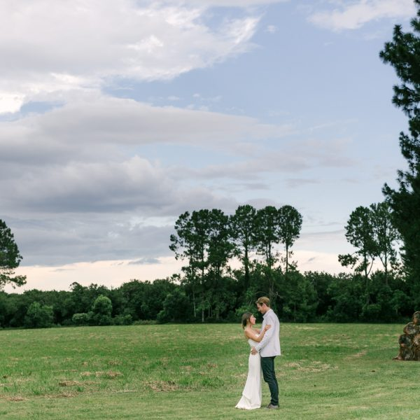 husband and wife stand in a field looking at one another