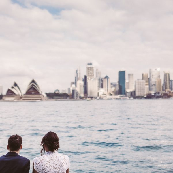 bride and groom sit by the water over looking the opera house in sydney