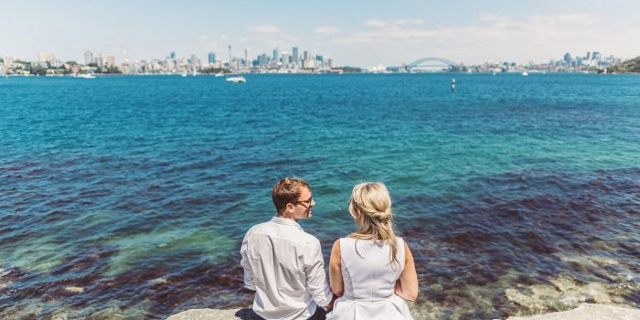 couple sit on rock on shark island overlooking sydney harbour bridge and sydney opera house