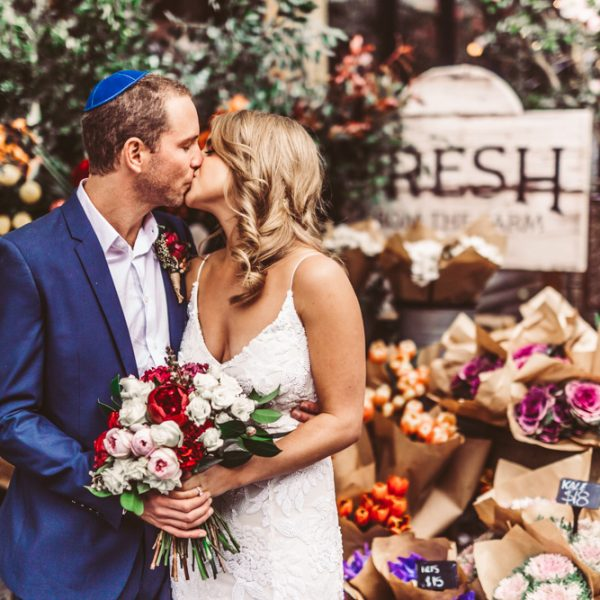 the ground of Alexandria wedding couple kissing in front of flower stand