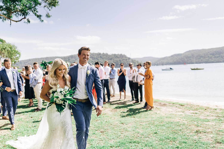 palm beach moby dicks wedding photographer sydney bride and groom walk down the aisle