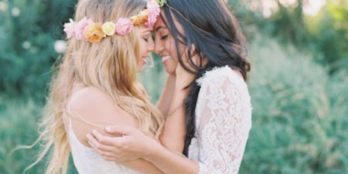 Same Sex marriage wedding photographer Sydney Australia two lesbian embrace in a field after getting married