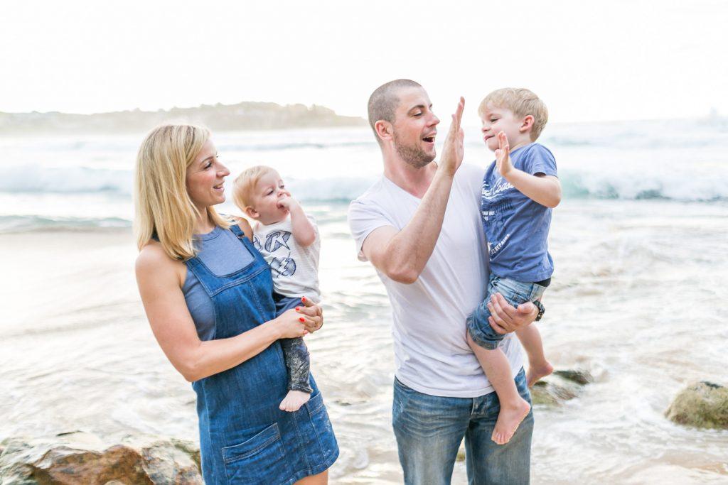 Family high five on bondi beach