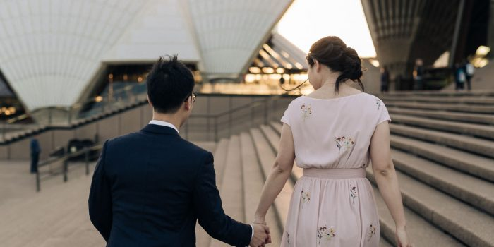 the opera house sydney pre wedding photographer couple hold hands and look at each other