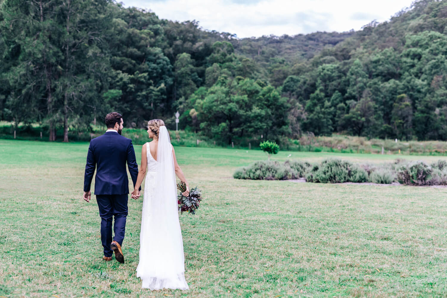 hunter valley wedding photographer bride and groom walking through the gardens at Redleaf Wollombi