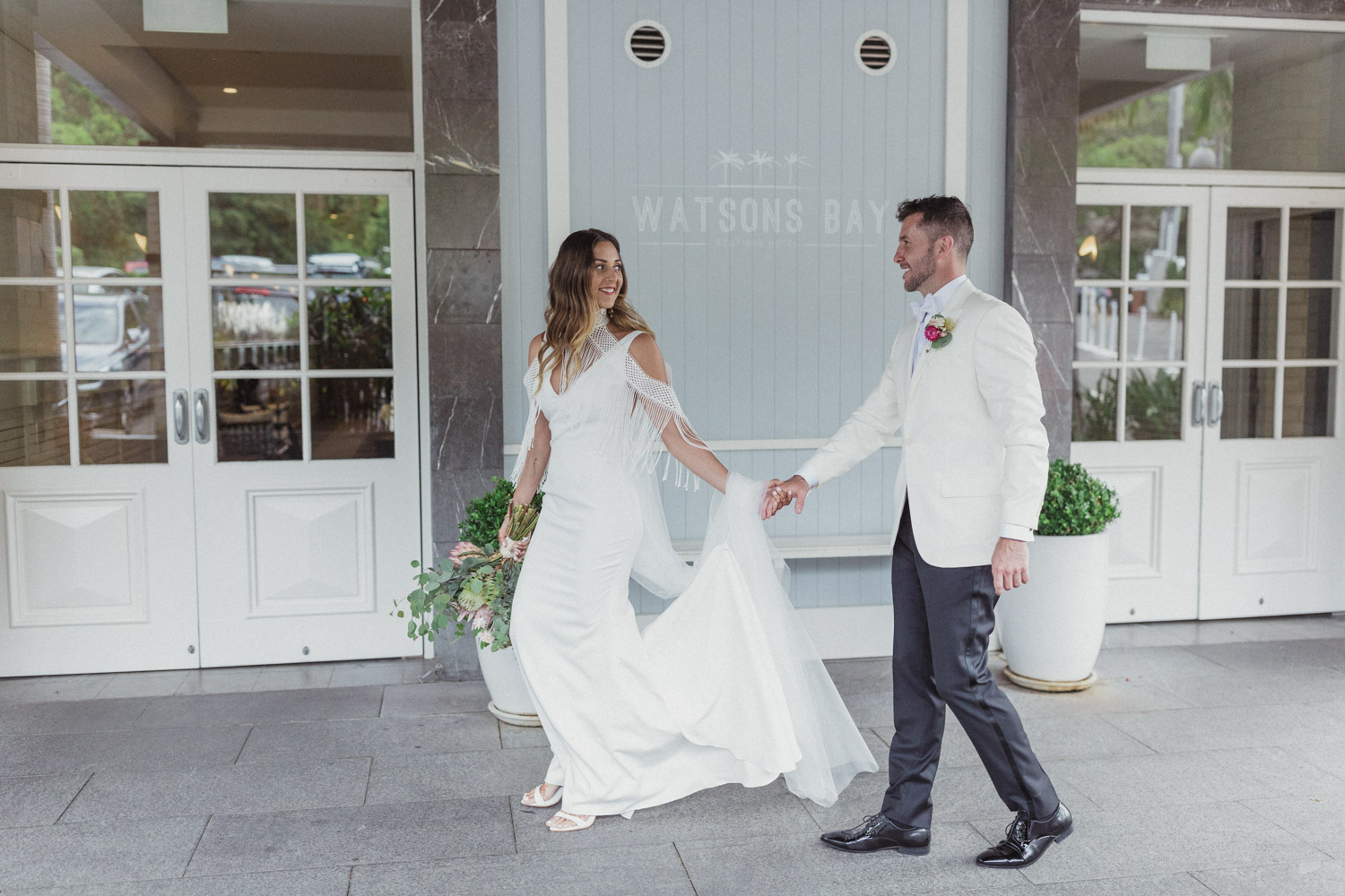 bride and groom standing outside the watsons bay hotel