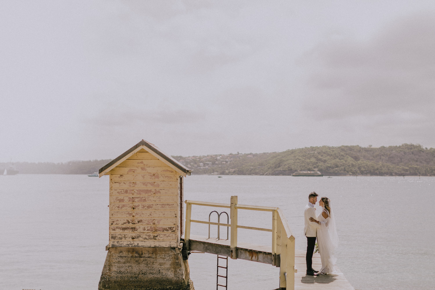 bride and groom stand on jetty at camp cove, sydney