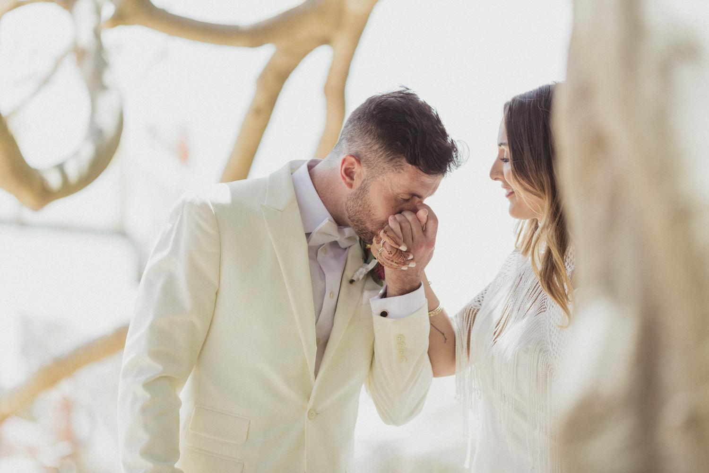 Groom kisses brides hand at camp cove, sydney