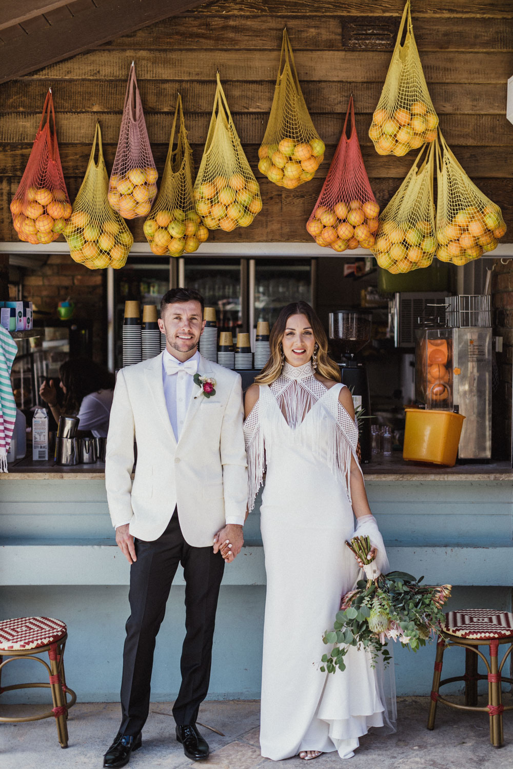 bride and groom stand under oranges at cafe at camp cove, sydney