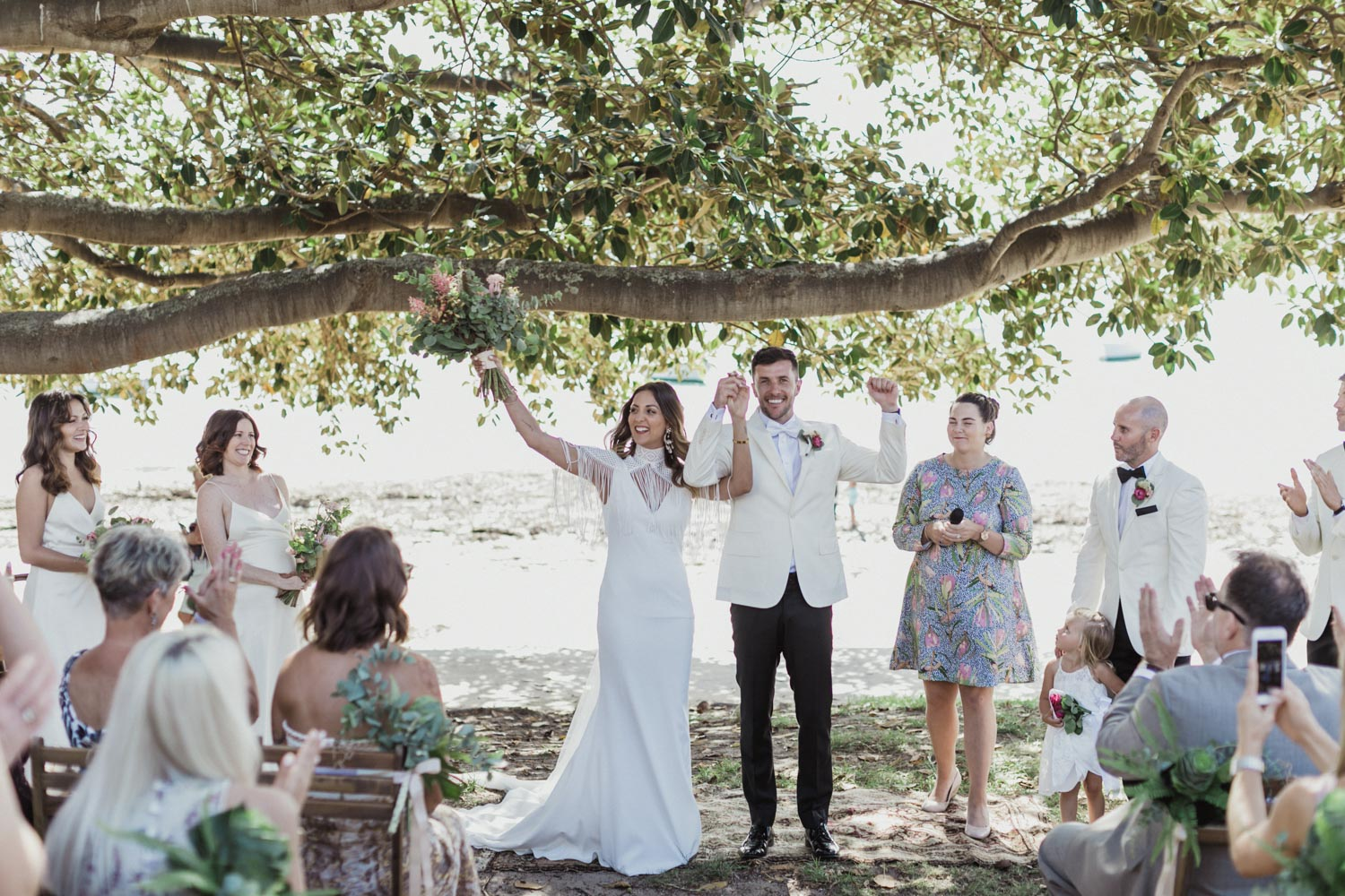 bride and groom stand under fig tree and have their wedding ceremony at Watsons Bay,Sydney
