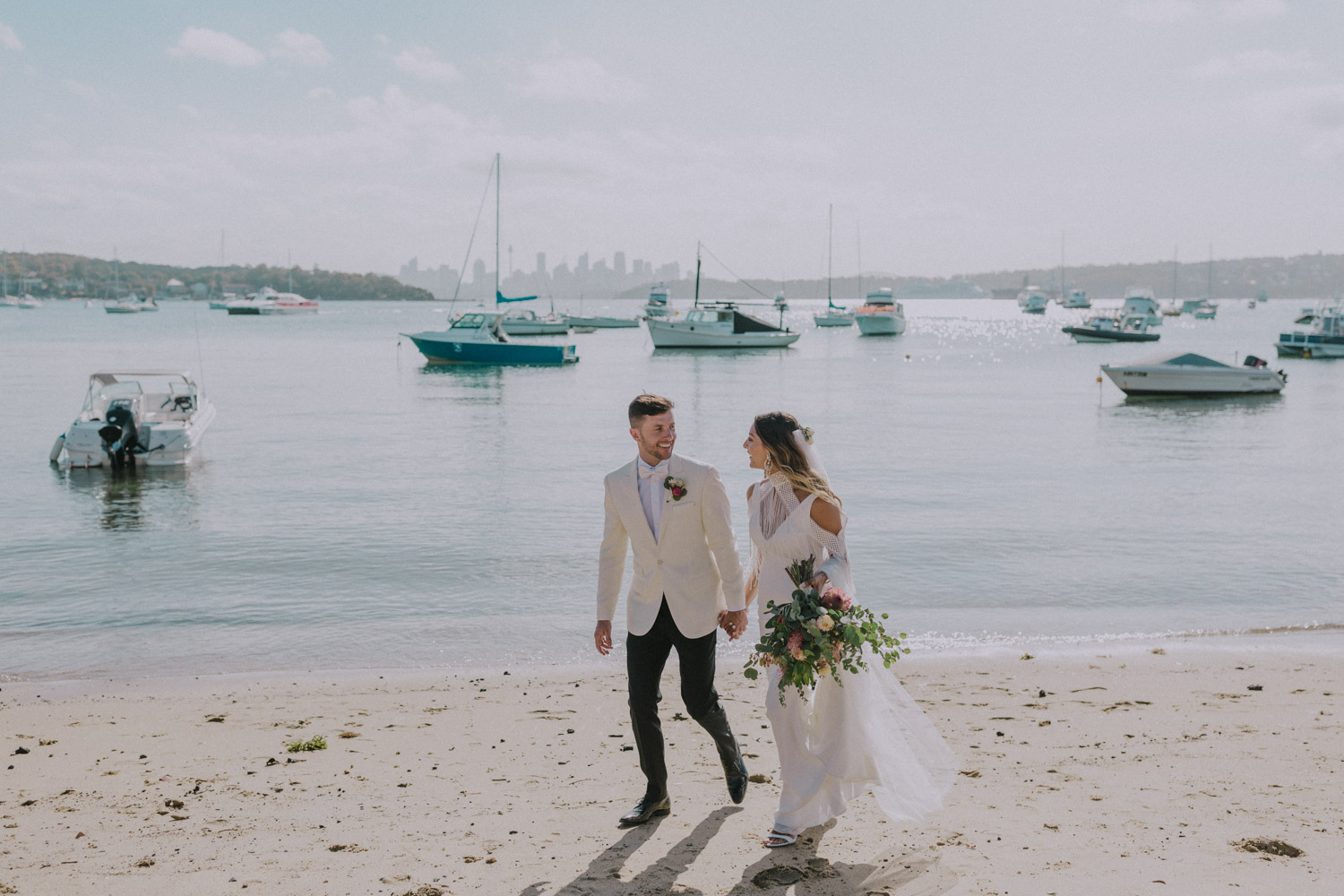 bride and groom walk on the beach at Watsons Bay,Sydney
