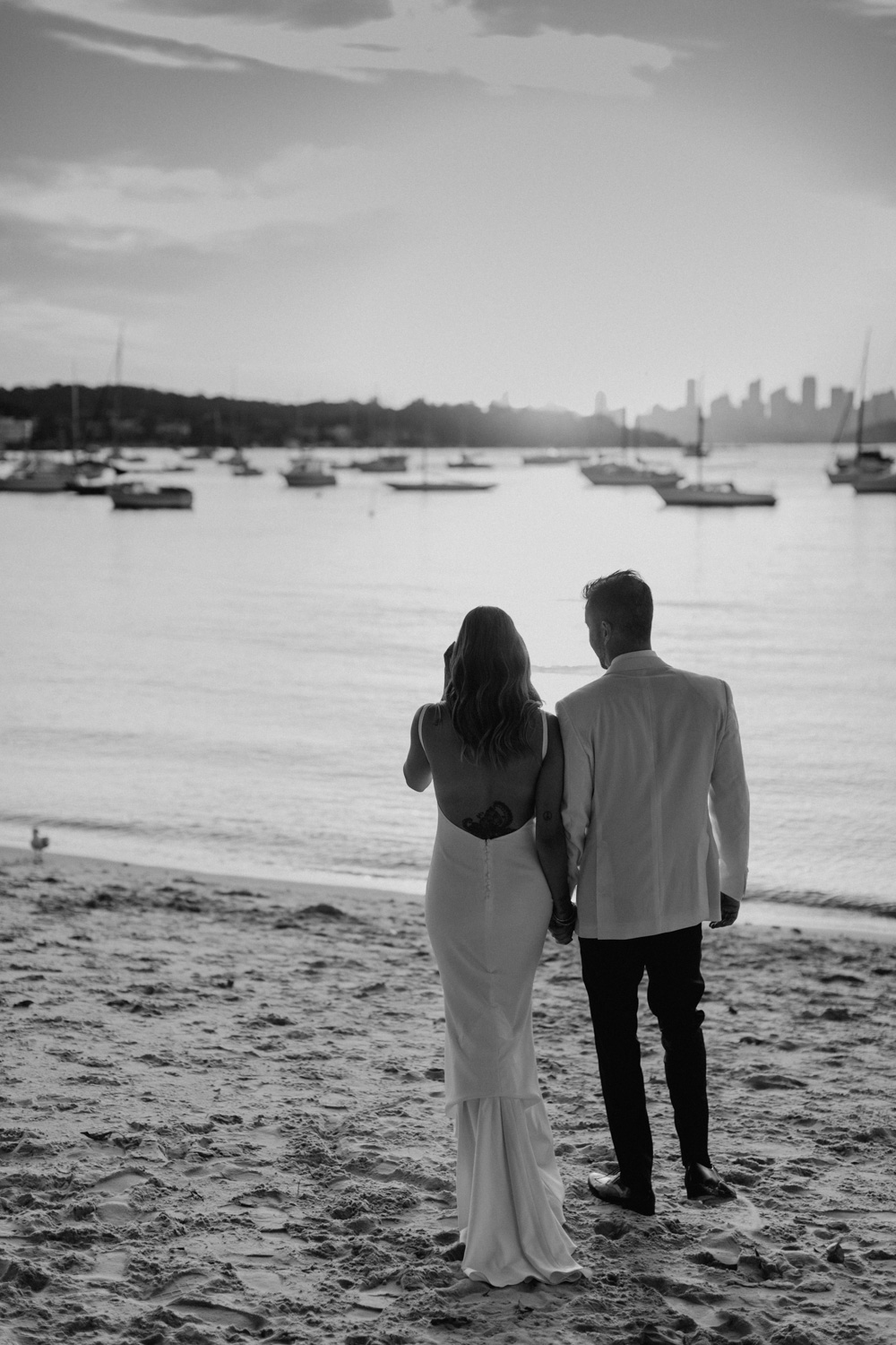 Sunset in black and white bride and groom walk on beach at Watsons Bay, Sydney