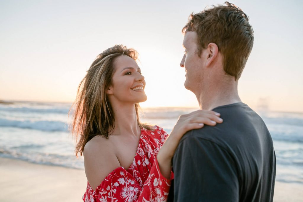 Pre wedding photography sydney of a couple on tamarama beach looking at each other at sunrise