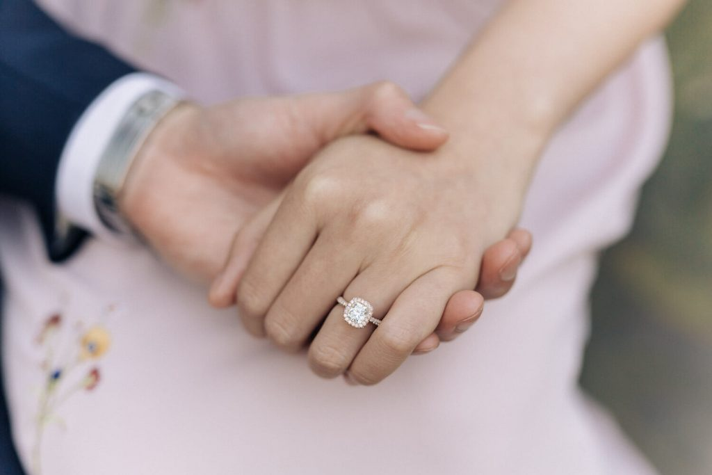 Pre wedding photography sydney a close up of an engagement ring. couple holding hands