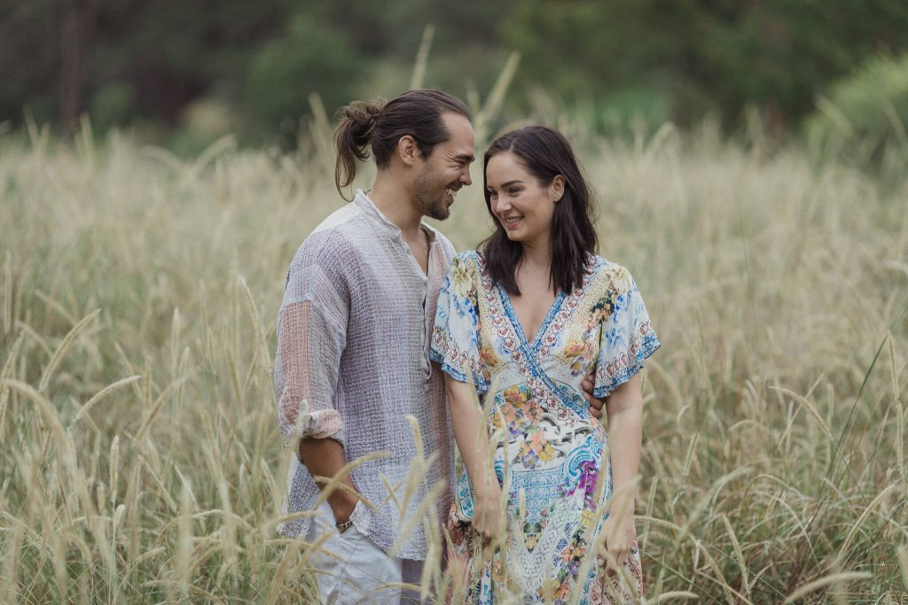 Pre wedding photography sydney of a couple in centennial park standing next to each other in the long grass laughing