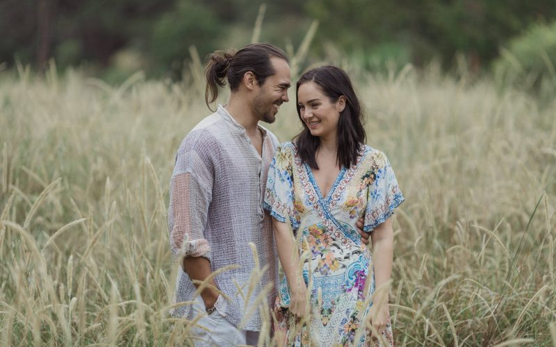 pre wedding photography sydney couple laughing together in the long grass at centennial park