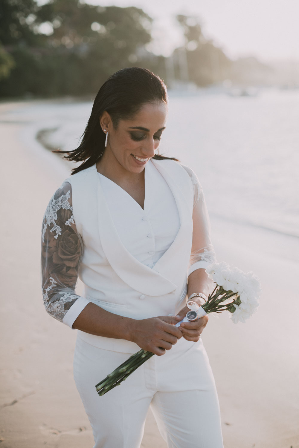 Beach House Avalon Sydney Same Sex Wedding Wedding Kat Rollings Photography bride looking at her flowers on the beach