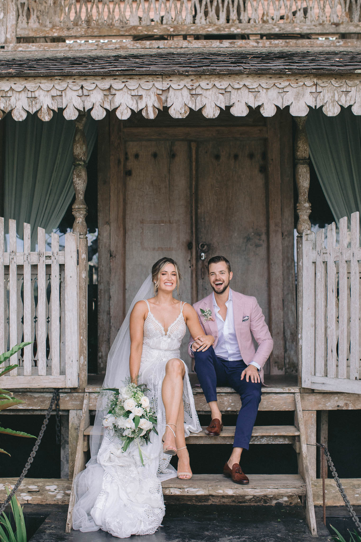 Khayangan Estate Bali Wedding Von Kiel Kat Rollings Photography bride and groom sitting on steps of a traditional balinese house