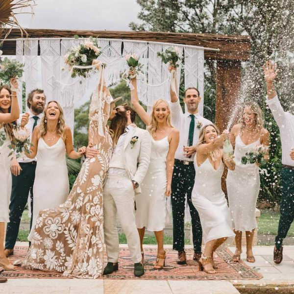 Tumbling Waters Retreat Stanwell Tops Wedding Emma Metcalf Scott Maggs Kat Rollings Photography bridal party celebrate by popping champagne while bride and groom kiss